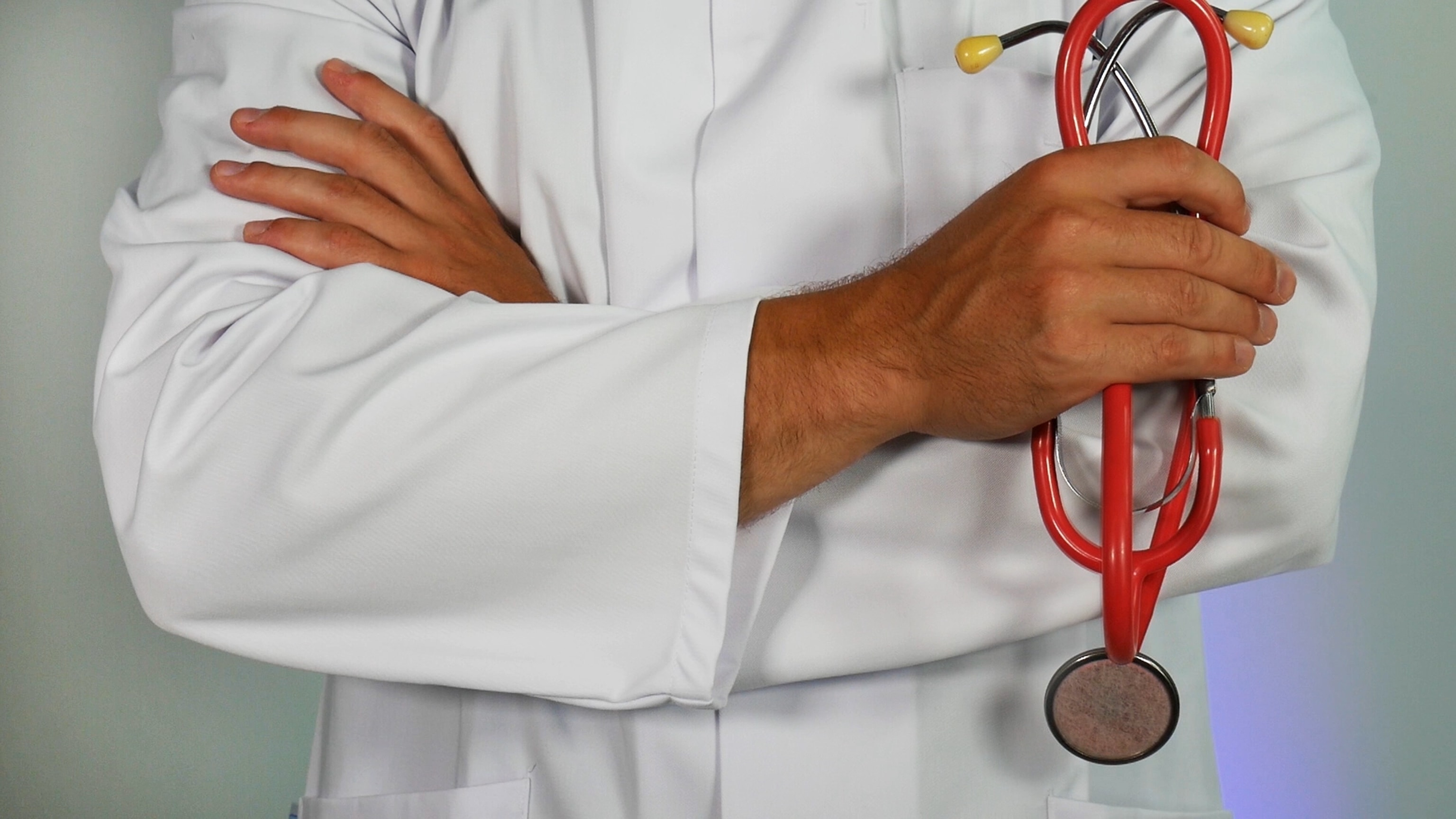 Doctor in white lab coat with arms crossed, holding a red stethoscope.